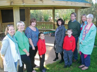 Janette Morris cuts the ribbon, watched by pupils and PTA members