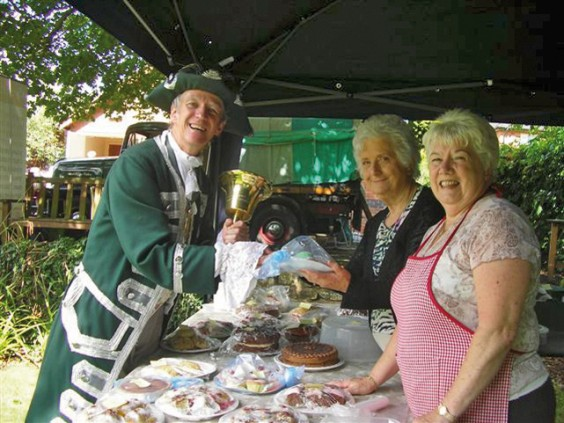 Town crier Kevin Ward checks out the cake stall