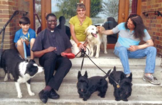 Revd Sibanda, community members and dogs